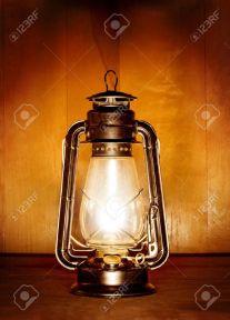 7846826-lámpara-de-aceite-viejo-luz-sobre-fondo-de-plancha-de-madera-